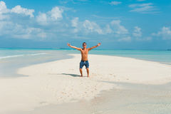 Happy attractive young male jumps on beach with white sand and o Royalty Free Stock Images