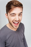 Happy attractive young man in grey pullover winking. Over white background Stock Photo