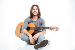 Happy attractive young man with guitar sitting and smiling Stock Image