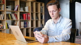 Happy attractive  young man  sitting and using smartphone in office. Young man , freelancer stock footage