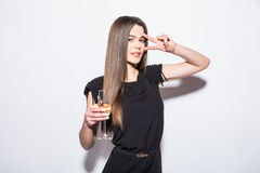 Happy attractive young woman in black dress holding star shaped balloon and drinking champagne Royalty Free Stock Photography