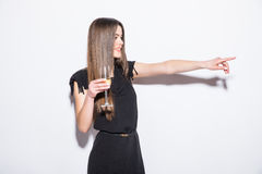 Happy attractive young woman in black dress holding star shaped balloon and drinking champagne and pointed on side Royalty Free Stock Photo