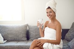 Happy attractive young woman with a cute friendly grin. Wearing a clean white towel around her hair holding a glass of pure fresh water laughing at camera royalty free stock photos