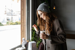 Happy attractive young woman drinking coffee in cafe. Happy attractive young woman in hat drinking coffee in cafe Royalty Free Stock Image