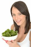 Happy Attractive Young Woman Holding a Plate of Fresh Raw Spinach Royalty Free Stock Photo