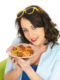 Happy Attractive Young Woman Holding a Plate of Spaghetti Meatballs Stock Photo