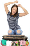 Happy Attractive Young Woman Kneeling on an Overflowing Suitcase Royalty Free Stock Photo