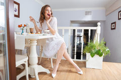 Happy attractive young woman sitting and eating dessert in cafe Royalty Free Stock Photos