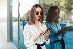 Happy attractive young woman in sunglasses looking at smartphone screen while walking in the city. Dressed in stylish clothes royalty free stock photo