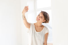 Happy attractive young woman with tatoo taking selfie. With smartphone standing near the window royalty free stock image