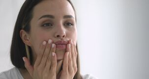 Happy attractive young woman touching pretty face after applying cream