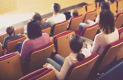 Happy audience expecting movie to begin Royalty Free Stock Images