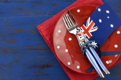 Happy Australia Day, January 26, theme table setting. With red polka dot plate and Australian flag decoration on dark blue wood background Stock Image