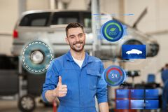 Happy auto mechanic man or smith at car workshop. Car service, repair, maintenance, gesture and people concept - happy smiling auto mechanic man or smith showing Stock Image