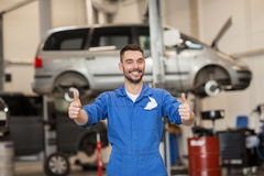 Happy auto mechanic man or smith at car workshop. Car service, repair, maintenance, gesture and people concept - happy smiling auto mechanic man or smith showing Royalty Free Stock Photos