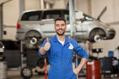 Happy auto mechanic man or smith at car workshop. Car service, repair, maintenance, gesture and people concept - happy smiling auto mechanic man or smith showing royalty free stock image