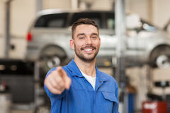 Happy auto mechanic man or smith at car workshop Royalty Free Stock Photo