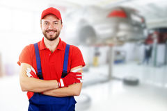 Happy auto mechanic standing in car service. Garage Royalty Free Stock Image