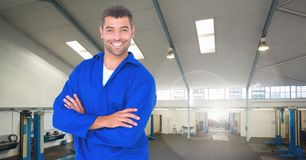 Happy automobile mechanic standing with arms crossed in workshop Royalty Free Stock Image