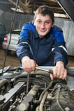 Happy automotive mechanic at work with wrench Royalty Free Stock Image
