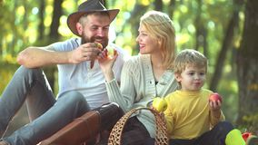 Happy Autumn Family. Smiling couple with child son walking over autumn natural background. Happy smiling young parents. With little son laying in autumn leaves stock footage