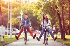 Happy autumn funny couple riding on bicycle. Happy autumn funny young couple riding on bicycle stock images