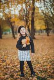 Happy autumn. A little girl in a red beret is playing with falling leaves and laughing. royalty free stock image