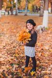 Happy autumn. A little girl in a red beret is playing with falling leaves and laughing. Girl in brown wool sweater and beret stock image