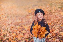 Happy autumn. A little girl in a red beret is playing with falling leaves and laughing. Girl in brown wool sweater and beret royalty free stock image