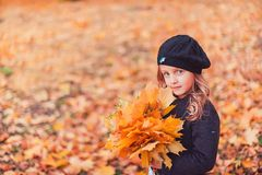 Happy autumn. A little girl in a red beret is playing with falling leaves and laughing. royalty free stock photo