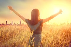 Happy autumn woman raising hands over sunset sky, enjoying life and nature. Beauty female on field looking on sun. Silhouette of girl in sunlight rays. Fresh