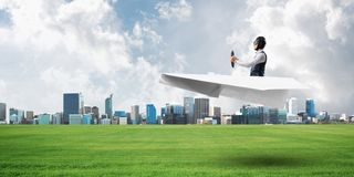 Happy aviator driving paper plane. Modern business center with high skyscrapers on background. Man in paper airplane flying low above ground. Megalopolis royalty free illustration