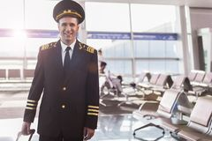 Cheerful smiling pilot in terminal. Happy aviator wearing uniform is locating in waiting hall and looking at camera with bright smile. Waist up portrait. Copy Stock Images