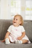 Happy babaygirl sitting on sofa Royalty Free Stock Photos