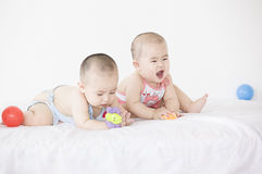 Happy babies. A pair of twinborn Chinese babies are very happily playing with toys in bed Royalty Free Stock Photo