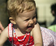 Happy baby. With red dress and necklaces Stock Photography