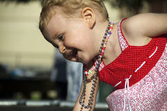 Happy baby. With red dress and necklaces Royalty Free Stock Image