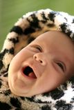 Happy baby. Image of a happy smiling baby in a fancy dress with hood Royalty Free Stock Image