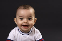Happy baby. Curious happy baby on black surface Stock Images