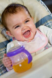 Happy Baby. A baby very happy to have her sippy cup stock photos