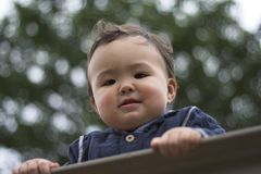 Happy baby. Young asian boy holding onto a rail at a park royalty free stock image