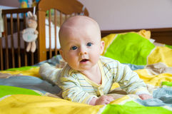 Happy baby. Four month happy baby lying on bed on belly royalty free stock photo