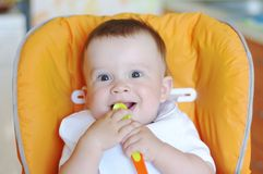 Happy baby age of 9 months with spoon. On baby chair Stock Photo