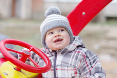 Happy baby age 1 year driving car on playground Stock Photography