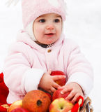 Happy baby with apples in winter park Royalty Free Stock Image