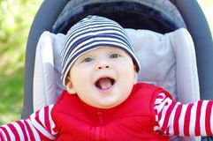 Happy baby on baby carriage. Happy baby age of 8 months on baby carriage Royalty Free Stock Images