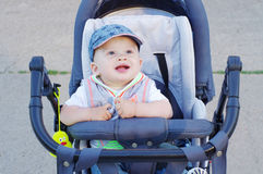 Happy baby on baby carriage Royalty Free Stock Image