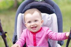 Happy baby on baby carriage in summer. Happy baby age of 10 months on baby carriage in summer Royalty Free Stock Photo