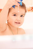 Happy baby. In the bath, swimming in the foam Stock Photos