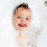 Happy baby in bath, swimming in foam. Baby shower Stock Photos